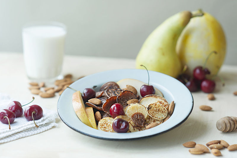 Tiny pancakes with pears, cherries, nuts in metal plate with fruit, milk. trending cereal pancakes