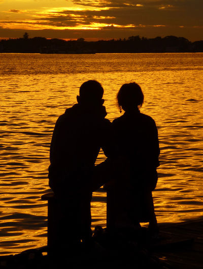 Silhouette friends standing by sea against sky during sunset