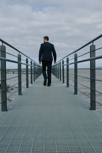 Rear View Of Man Walking On Pier Over Sea Against Sky