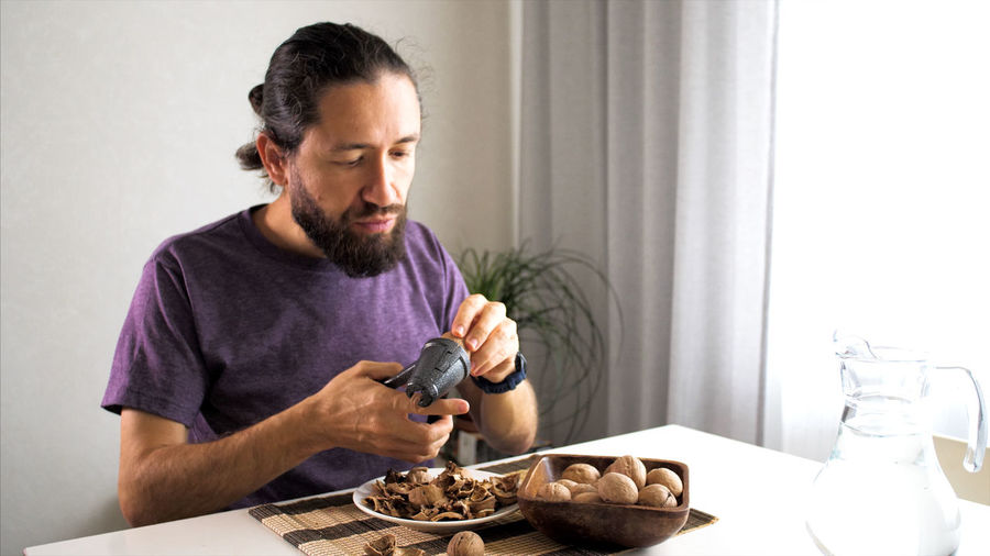 Man crushing walnut at home
