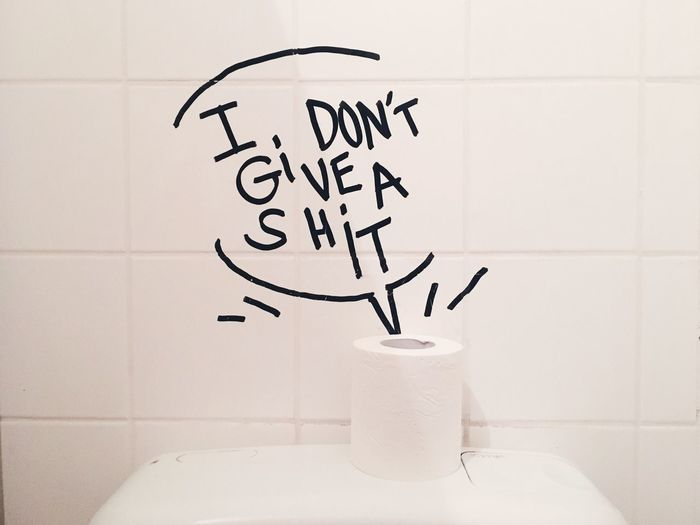 Text On Wall With Toilet Paper In Bathroom