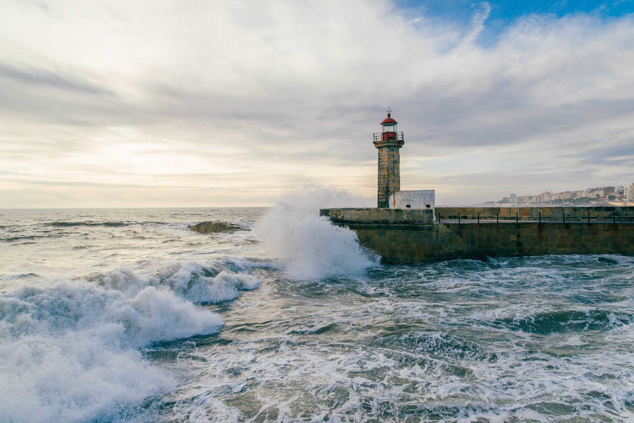 sea, water, wave, lighthouse, built structure, architecture, tower, sky, nature, building exterior, cloud - sky, motion, power in nature, breaking, beauty in nature, no people, outdoors, day, horizon over water, force