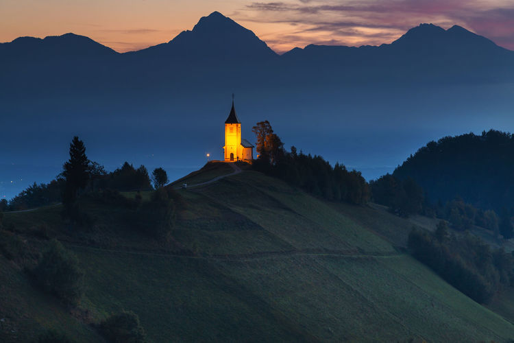 Scenic view of landscape against mountain during dusk