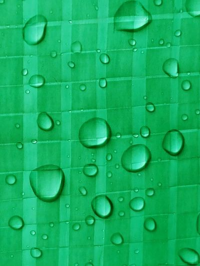 Full frame shot of water droplets on green plastic surface