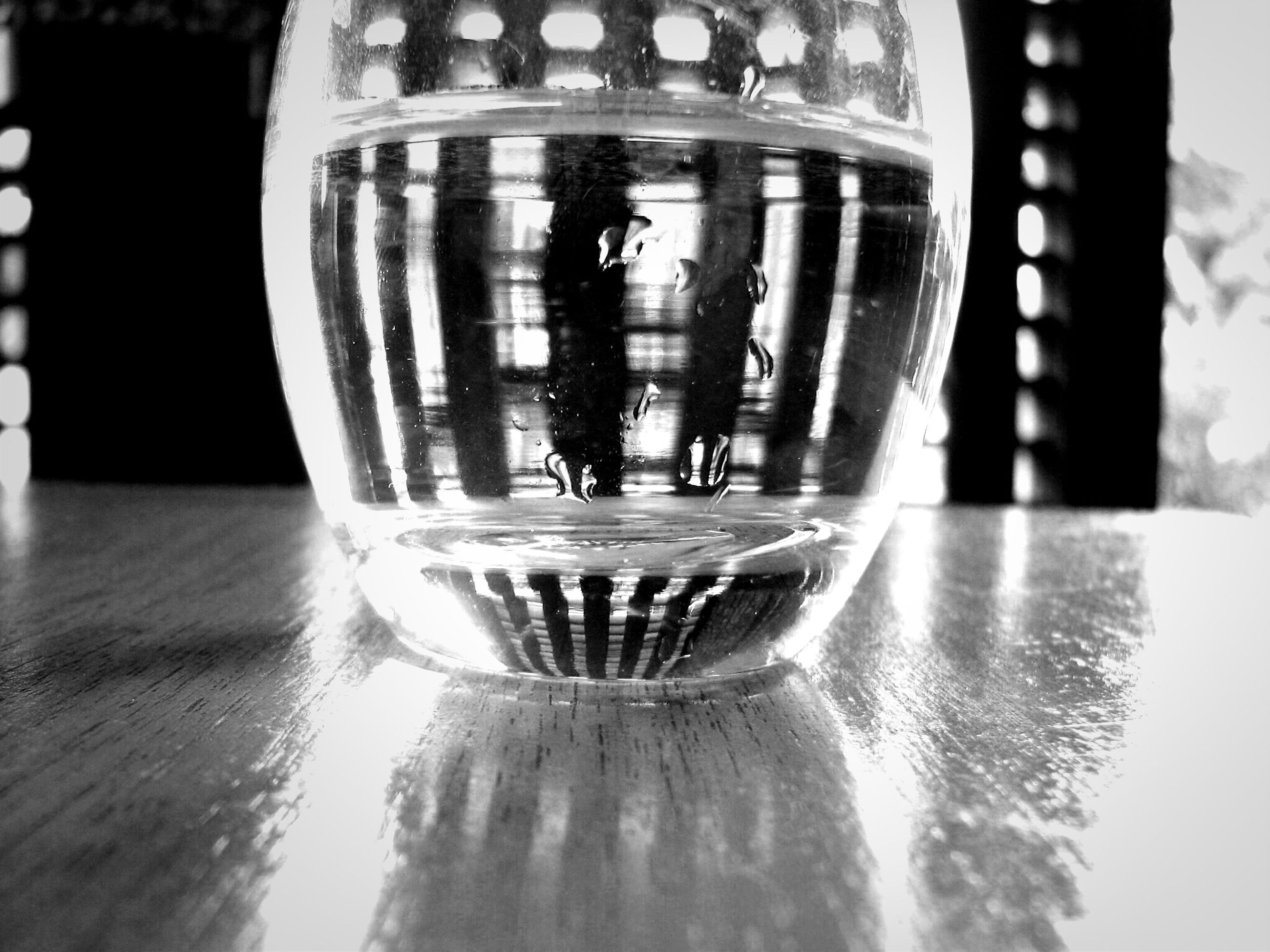 indoors, glass - material, drinking glass, reflection, close-up, transparent, refreshment, focus on foreground, lighting equipment, water, illuminated, drink, wineglass, motion, splashing, table, alcohol, glass, no people, selective focus