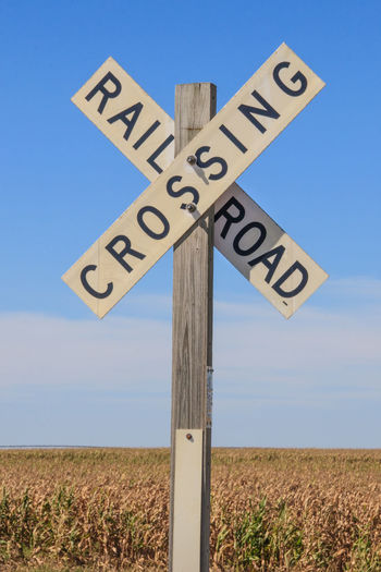 Railroad Sign Kansas Shallow Depth Of Field Signs Blue Close-up Communication Day Direction Field Grass Guidance Information Sign Nature No People Outdoors Railroad Road Sign Rural Scene Sky Text Vertical Yellow