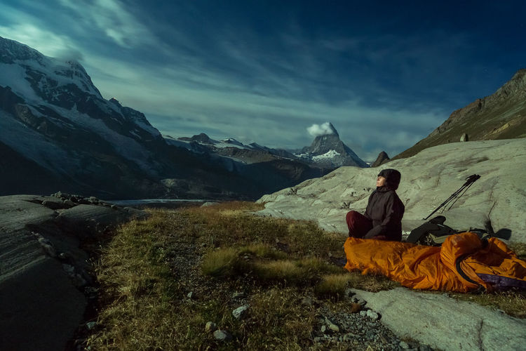 Mature Woman Sitting On Field Amidst Mountains Against Cloudy Sky