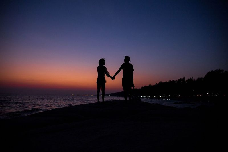 Silhouette of couple holding hands while standing at beach against sky during sunset
