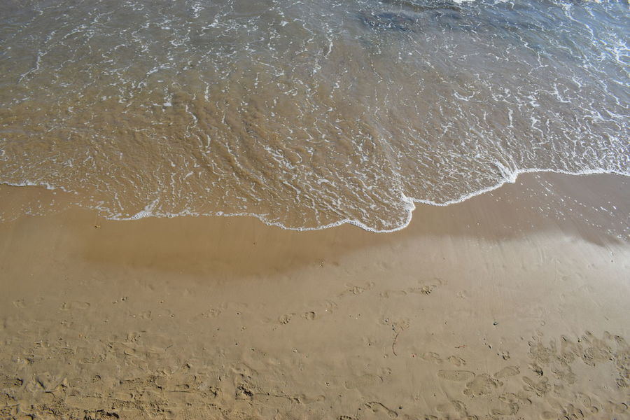 a wave on wet sand Sandy Beach Wave Surf Sea Shore Wet Sand Yellow Sand Beach Aerial View Looking Down Water Waterfront Water Backgrounds Spraying Close-up Sky Abstract Backgrounds Abstract Wave Pattern