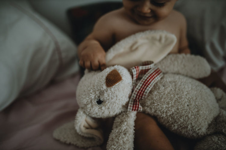 Midsection of boy holding toy sitting on bed at home