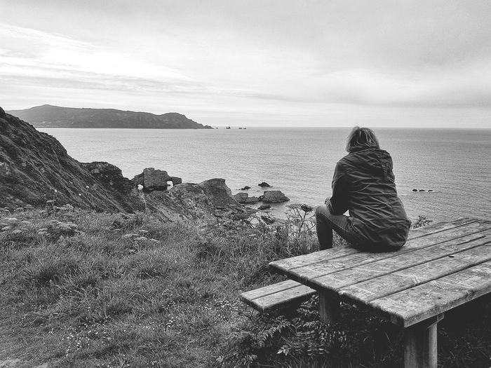 Rear view of woman sitting on bench at sea shore against sky