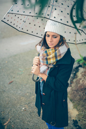 Portrait of young beautiful girl under a umbrella in an autumn rainy day Woman Cold Winter Hat Scarf Rain Girl Young Female Outdoors Autumn Fall Real People Caucasian One Person Serious Solitude Pensive Coat Alone Relax Concentration Umbrella Rainy Vertical