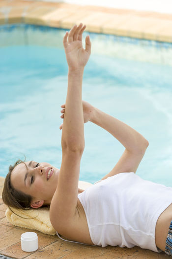High Angle View Of Woman Applying Cream While Lying At Poolside