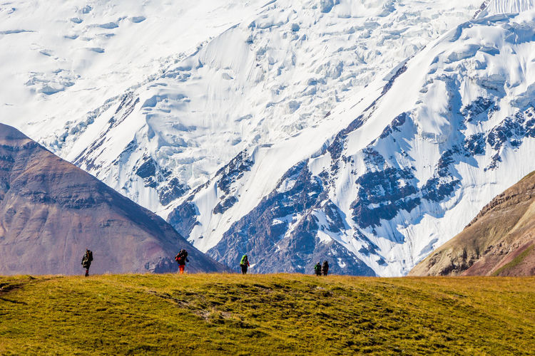 Hikers on landscape against snowcapped mountain