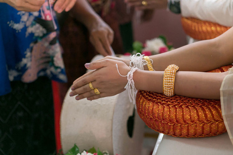 Cropped hands of bride praying in temple