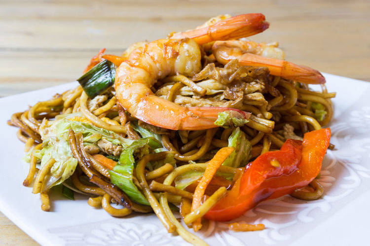 Close-up of shrimps with noodles served on table