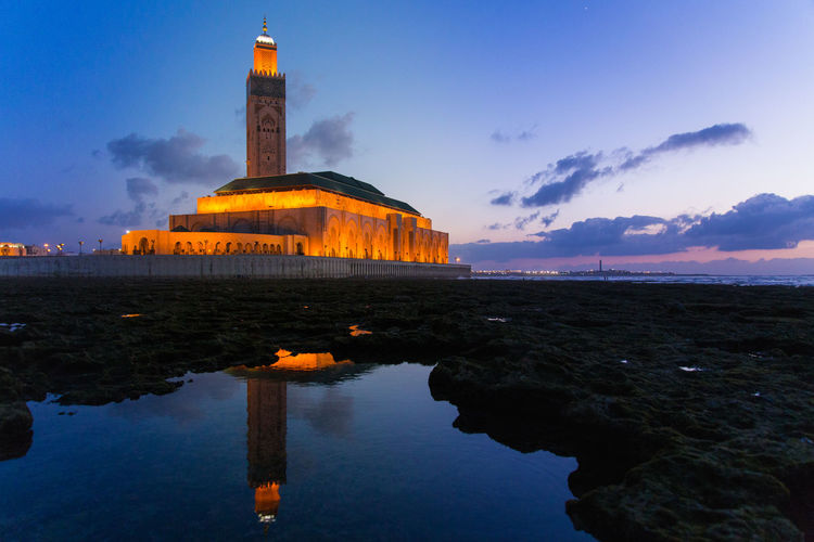 Reflection of hassan ii mosque in water during sunset