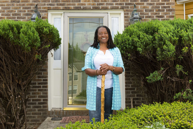 Portrait of smiling woman standing against house