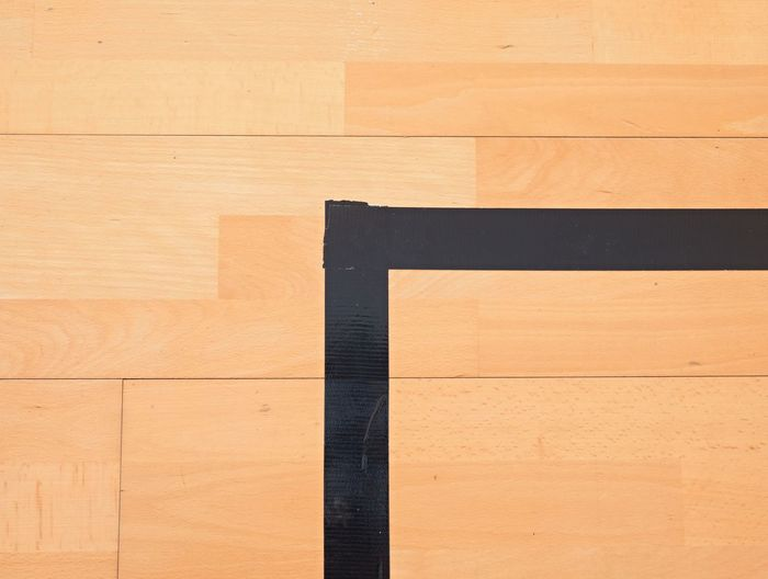 Black corner. worn out wooden floor of sports hall with colorful marking lines