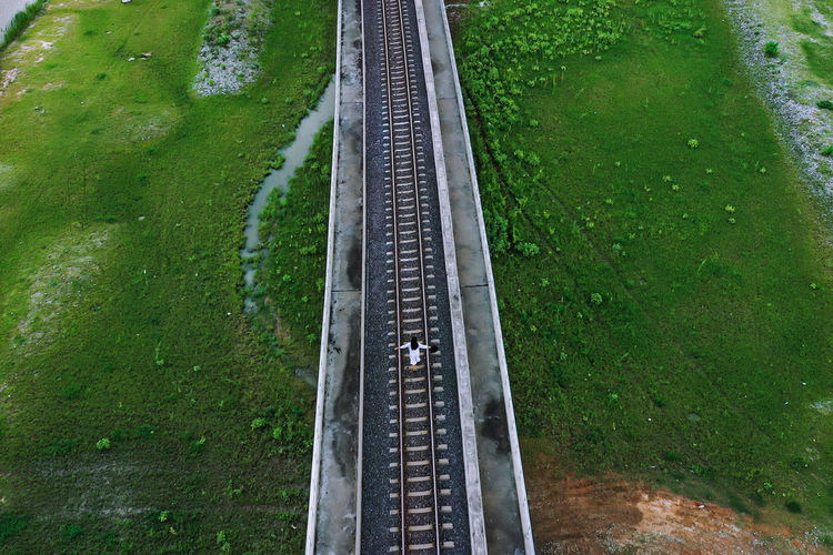 High angle view of woman walking on railroad track