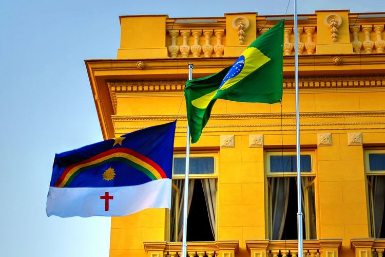 Low Angle View Of Brazilian Flag Against Building In City