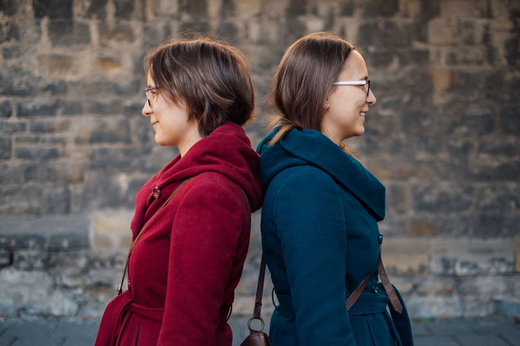 Smiling sisters standing back to back against stone wall