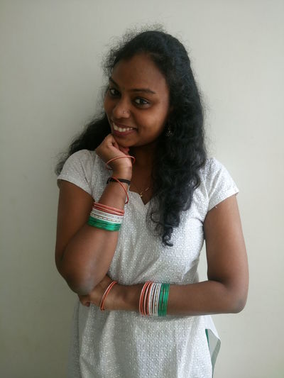 Portrait of smiling young woman wearing tricolor bangles standing against wall
