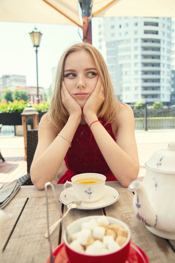 Portrait of young woman sitting on table