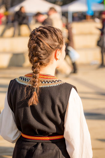 PERNIK, BULGARIA - JANUARY 26, 2018: Female dancer in Bulgarian folklore costume shows Proudly shows her fishtail hairstyle in sunny winter day at the International Festival of Masquerade Games Surva Event Games Hair Kukeri Kukeri, Bulgaria Festival Fishtail  Hairstyle Masquerade Surva