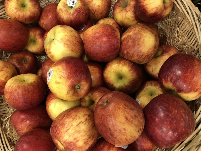 High Angle View Of Apples In Wicker Basket For Sale At Market Stall