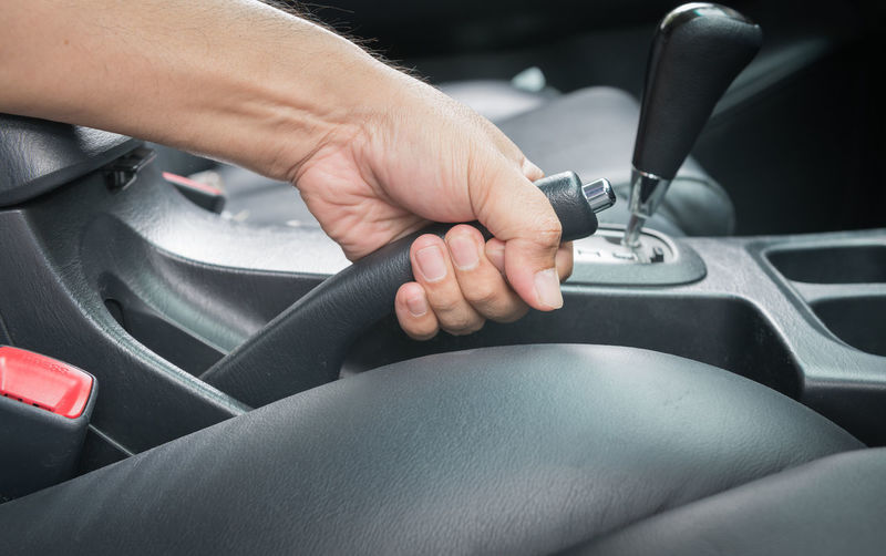 Cropped hand holding gearshift in car