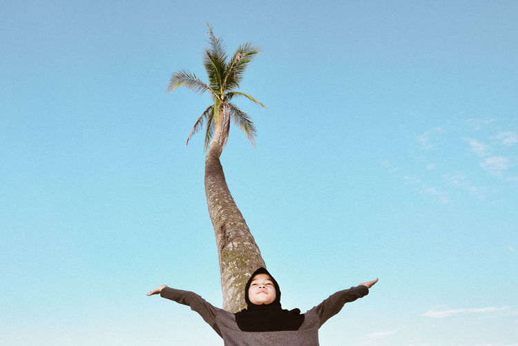 Low angle view of teenage girl with arms outstretched standing against blue sky