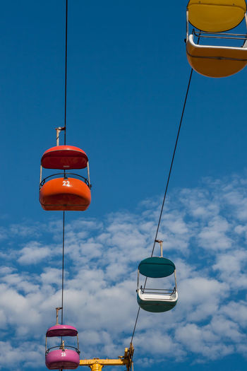 Low Angle View Of Overhead Cable Cars Against Blue Sky
