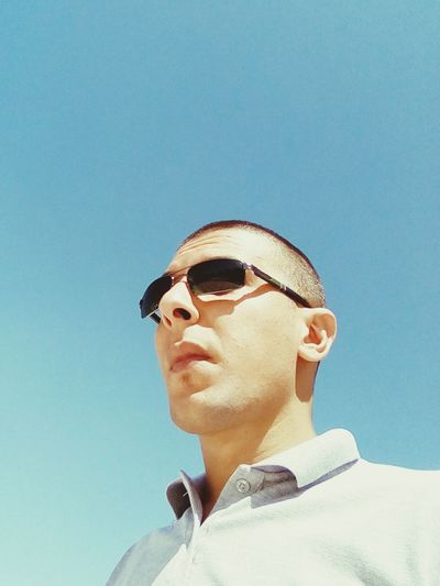 Low Angle View Of Young Man Wearing Sunglasses Standing Against Clear Sky
