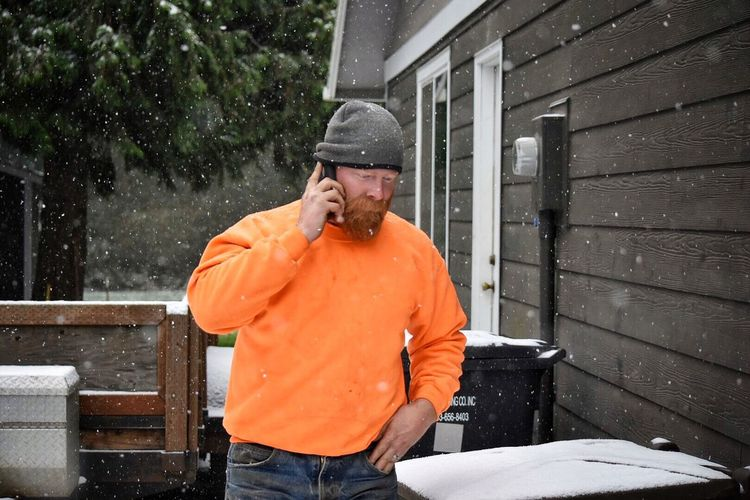 Midsection Of Man Using Phone On Snowy Day