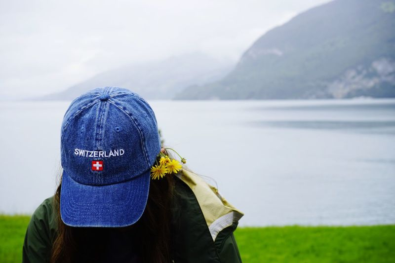Close-Up Of Young Woman Wearing Cap While Looking Down At Lake