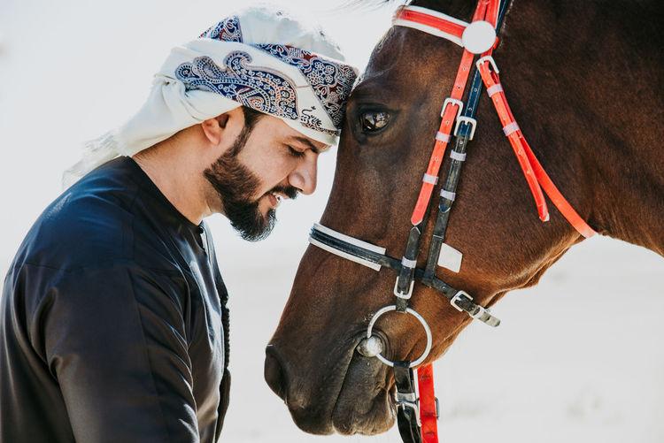 Man with horse in desert against sky