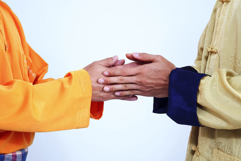 Midsection Of Friends Wearing Traditional Clothing While Holding Hands Against White Background