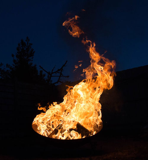 Close-up of bonfire against clear sky at night