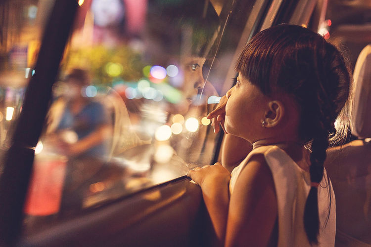 Close-up of cute girl looking through car window at night