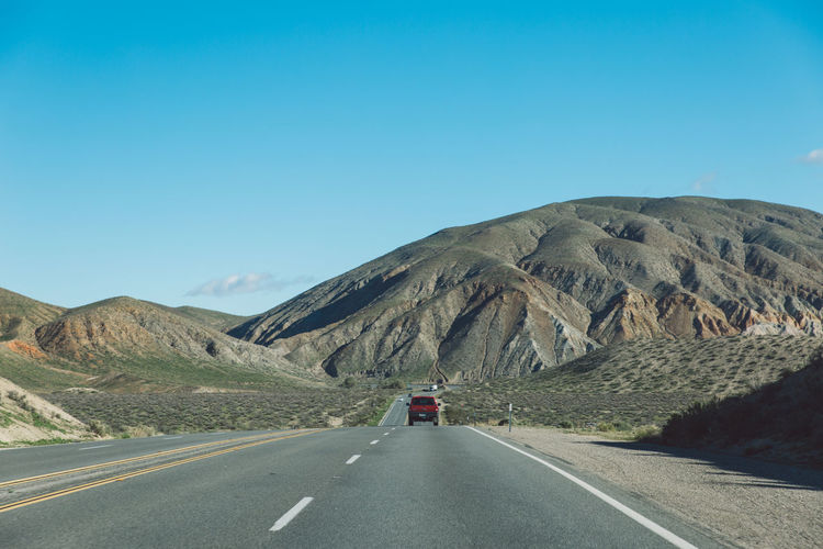 Vehicles on road by mountain against clear blue sky