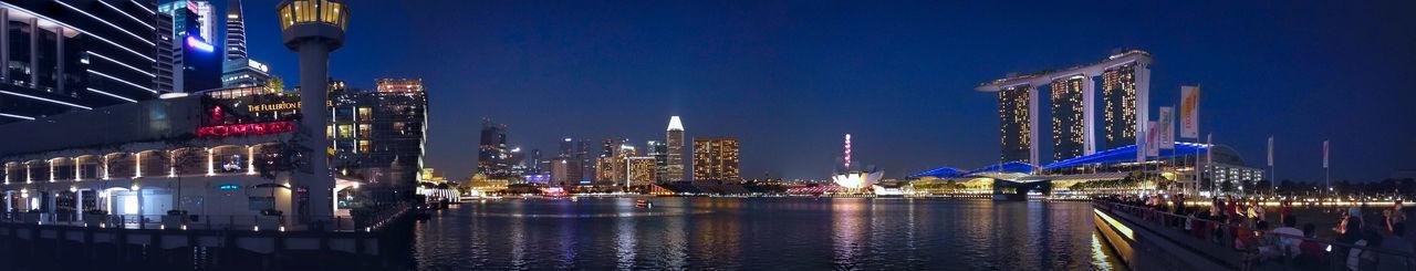 Panoramic view of harbor and illuminated buildings at night