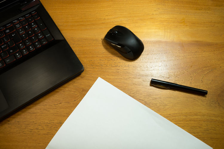 High Angle View Of Laptop And Mouse With Paper By Pen On Wooden Table