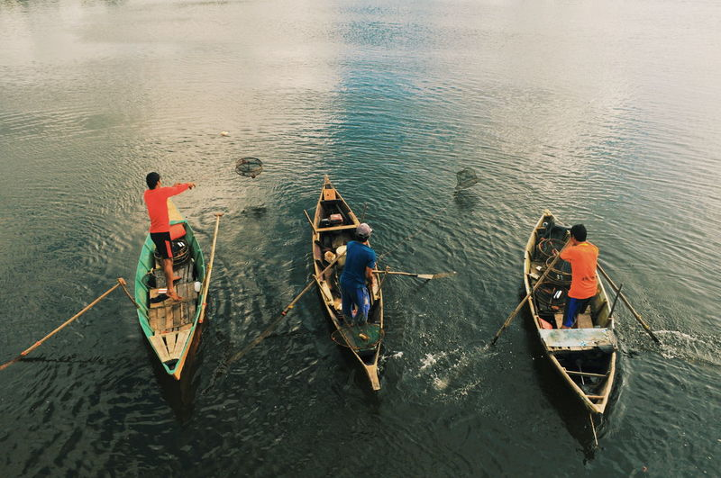 Rear view of men boating on lake