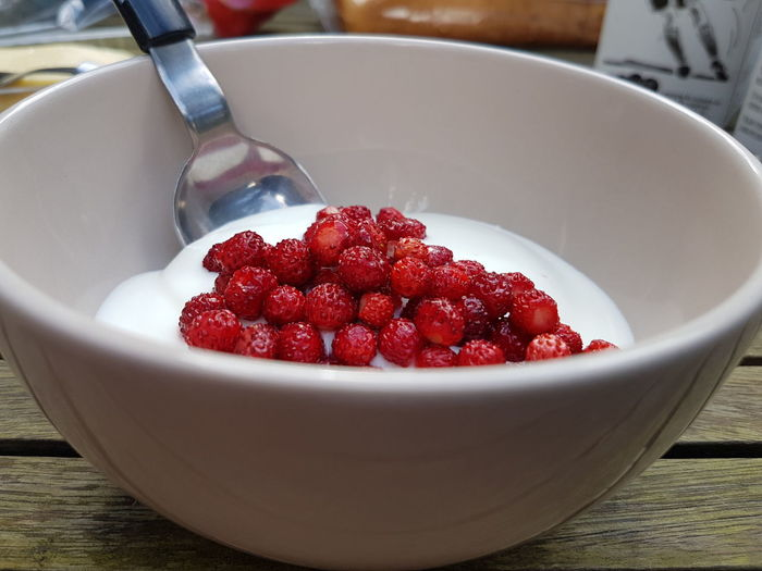 Close-up of red fruits and yogurt in bowl on table