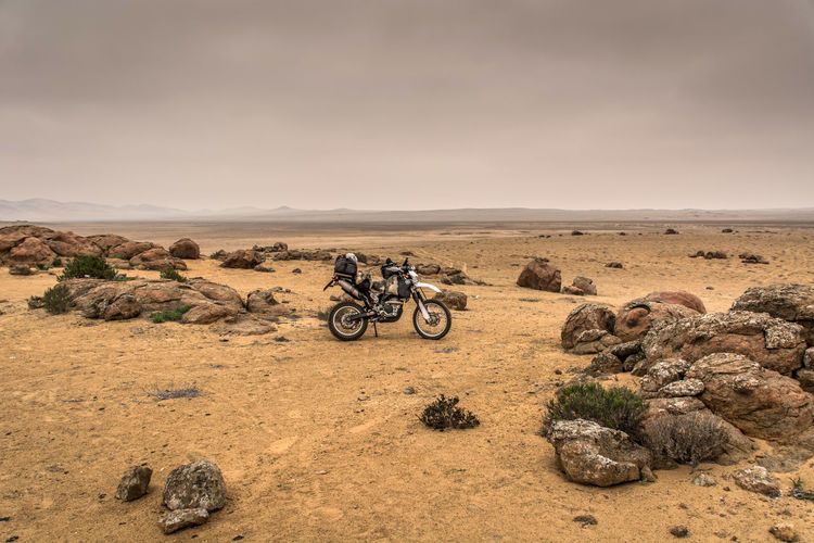 Bicycle parked on rock in desert against sky