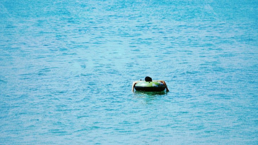 Person Relaxing On Inflatable Ring In Sea