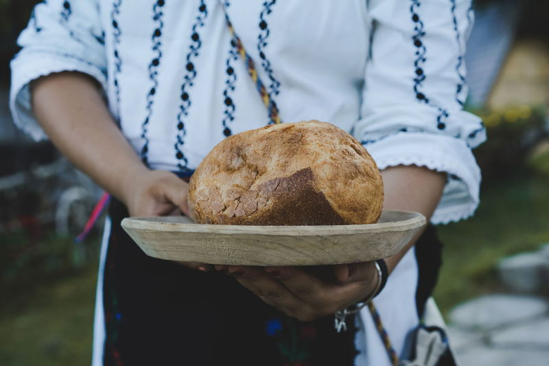 Close-up of hand holding bread on plate