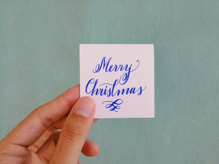 Close-up of hand holding paper with christmas text against wall