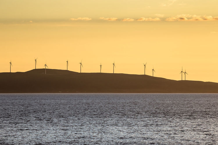 Scenic view of windmill field by the sea